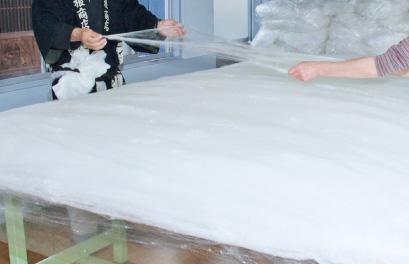職人さんが息を合わせて手挽きます。 この真綿の層が温度と湿度の調整のポイントです。